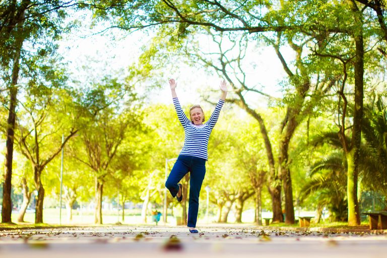 An older woman dancing alone in the park.