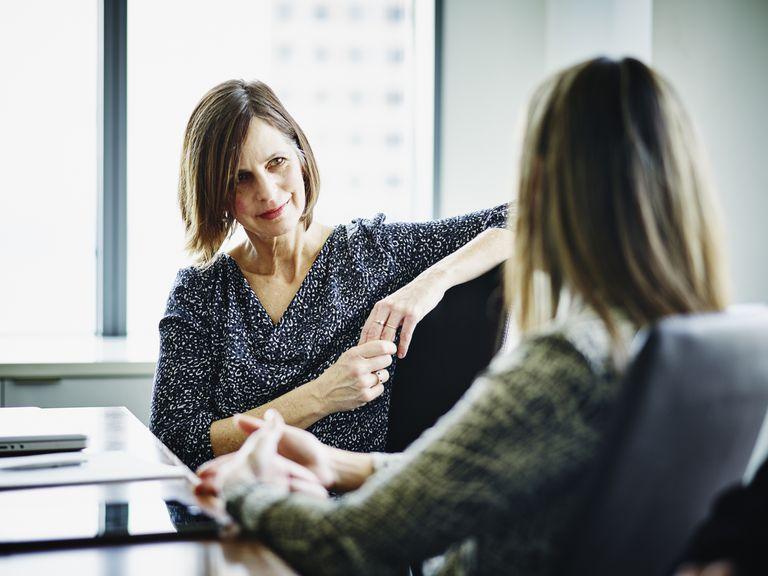 Two women talking in a business setting.