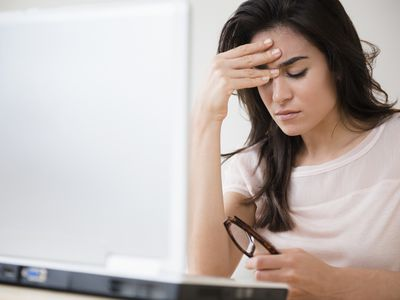 Stressed woman rubbing her forehead at laptop