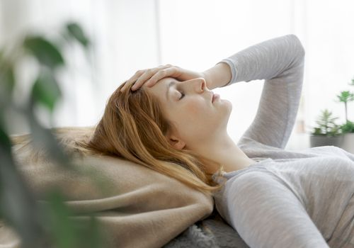 A woman lies on a pillow with her eyes closed and hand on her head.