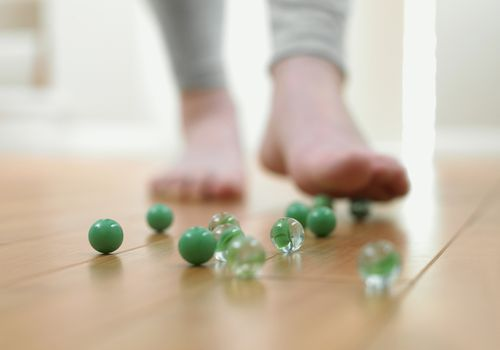 Child's food hovering over marbles on a wood floor