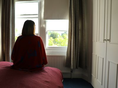 Woman wearing maroon robes, sitting on pink sheets staring outside into a window exposing trees