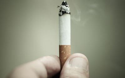 person holding a burning cigarette
