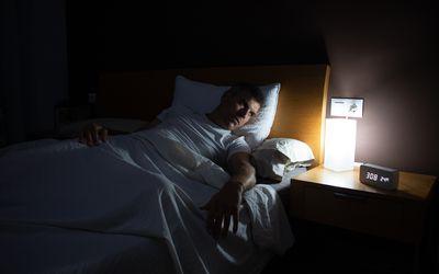 Man awake staring at alarm clock