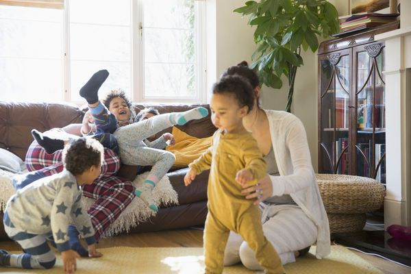 Young family in pajamas playing in living room