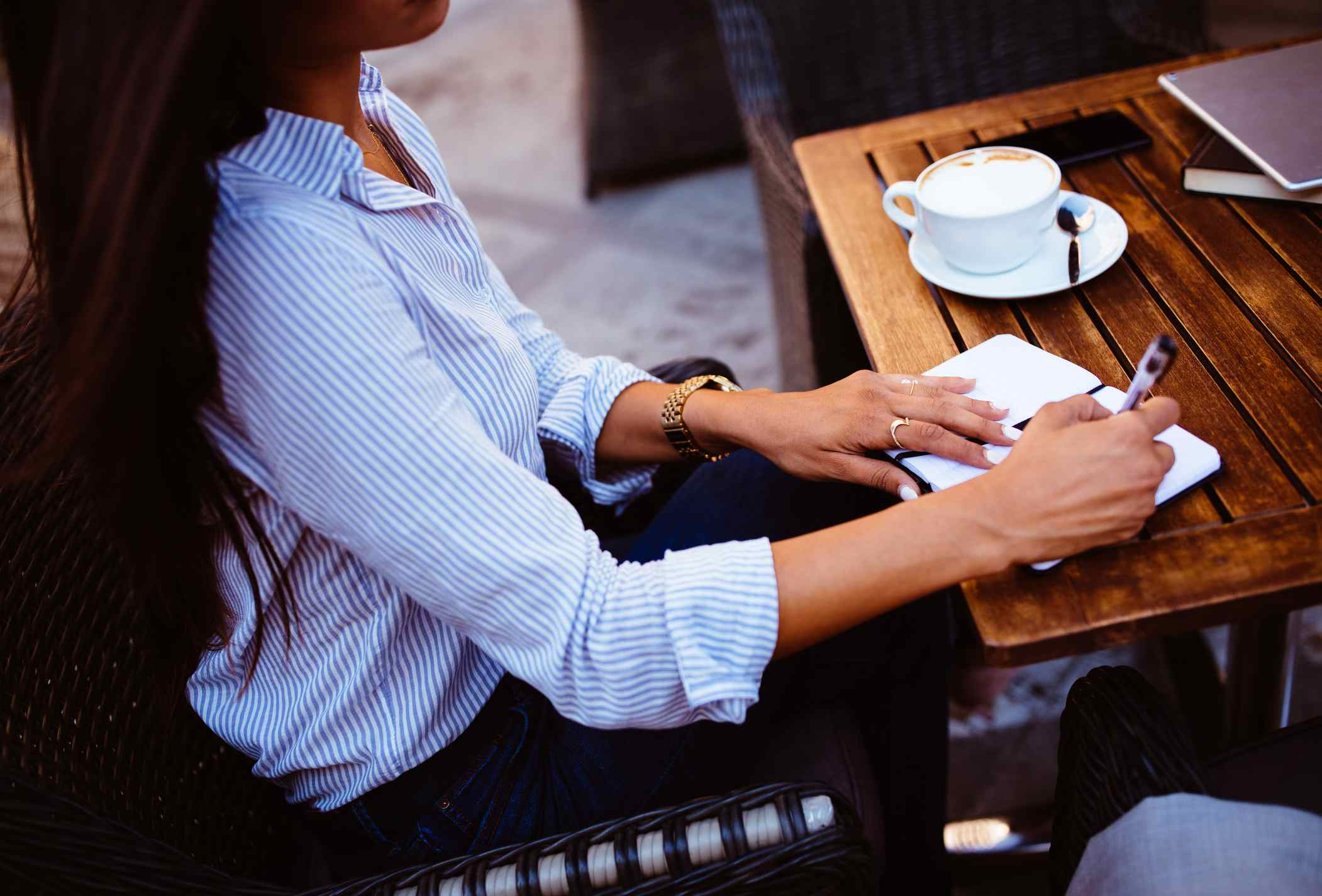 Young businesswoman making notes in diary sitting at urban cafe