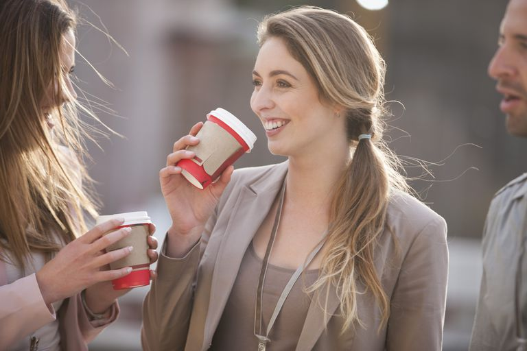 A woman drinks a cup of coffee with her co-workers