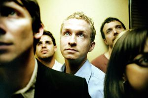 People in elevator, close up (focus on blond man)