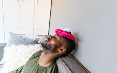 A Black man rests his head on the back of his couch with a pink ice pack on his head.
