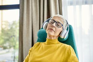 Older woman with headphones on peacefully dozing off to sleep