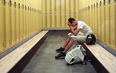 Teenage boy (15-17) in football uniform, sitting in locker room