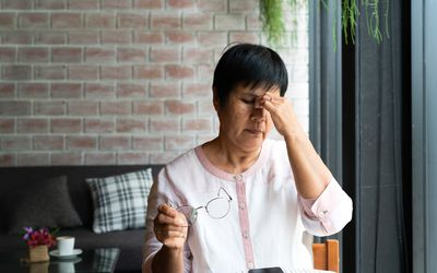Old woman headache while using smartphone, healthcare concept