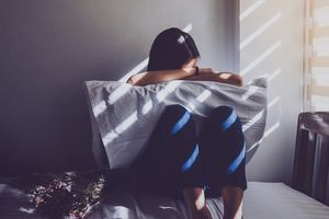 sad woman sitting on bed at home
