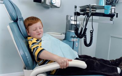 Scared child gripping the arms of chair in a dentist's office