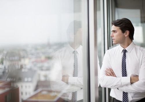 Businessman with crossed arms looking out office window