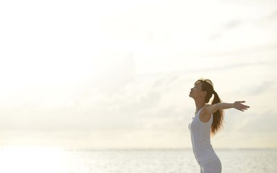 woman standing next to ocean with arms open