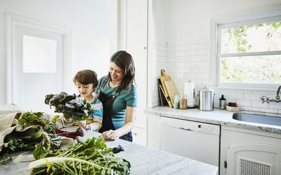 A young child and an adult in the kitchen look at fresh vegetables.
