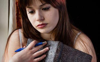 sad woman writing in journal