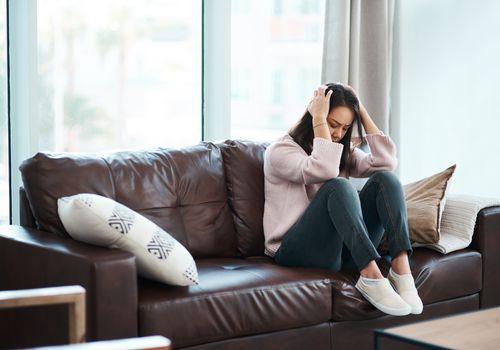 Shot of a young woman experiencing mental anguish at home