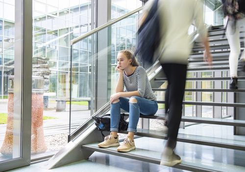 Lonely girl sitting on stairs at college.