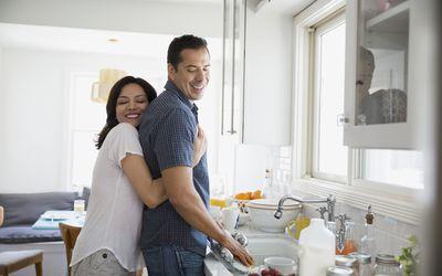 Affectionate brunette couple hugging at kitchen sink