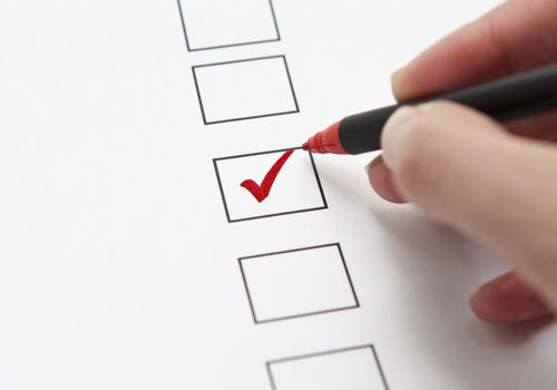 person checking a checkbox with red pen