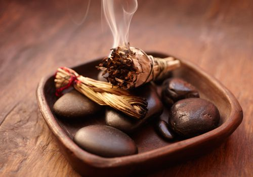 Bowl of rocks with burning sage.