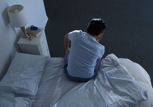 Man sitting on edge of bed with his face in his hands at night time