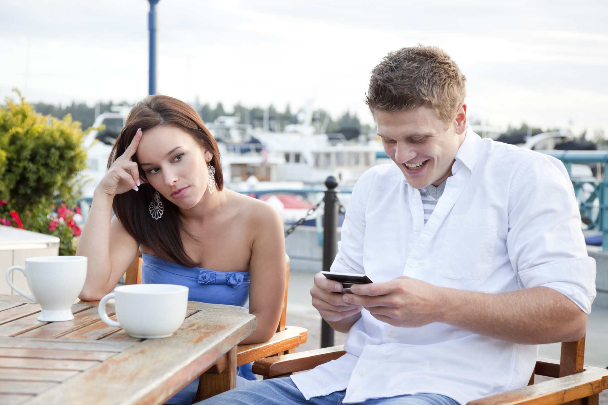 Young woman looking irritated by her date who is preoccupied with his phone