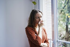 Woman looking anxiously out window