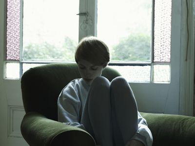 sad girl sitting in armchair