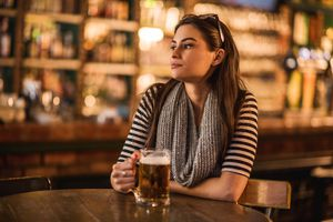 young woman sitting in a bar with a glass of beer in hand