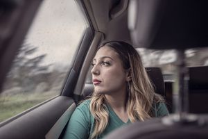 Woman riding in a car looking out the window.