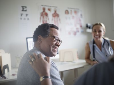 Smiling senior man talking with wife and doctor in examination room