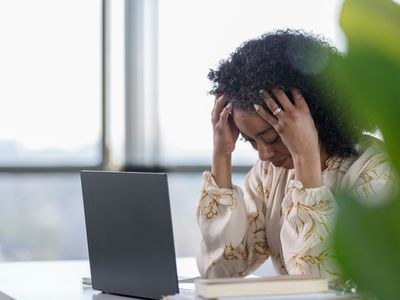 Stressed woman looking at a laptop.