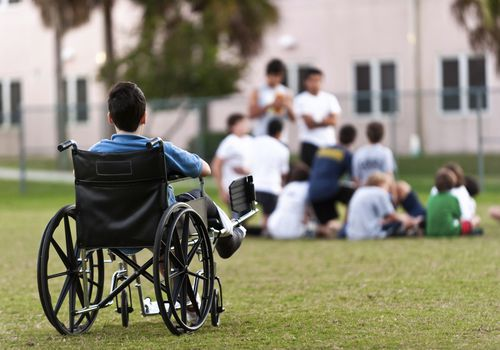 Child in a wheel chair looking at a group of boys in the distance
