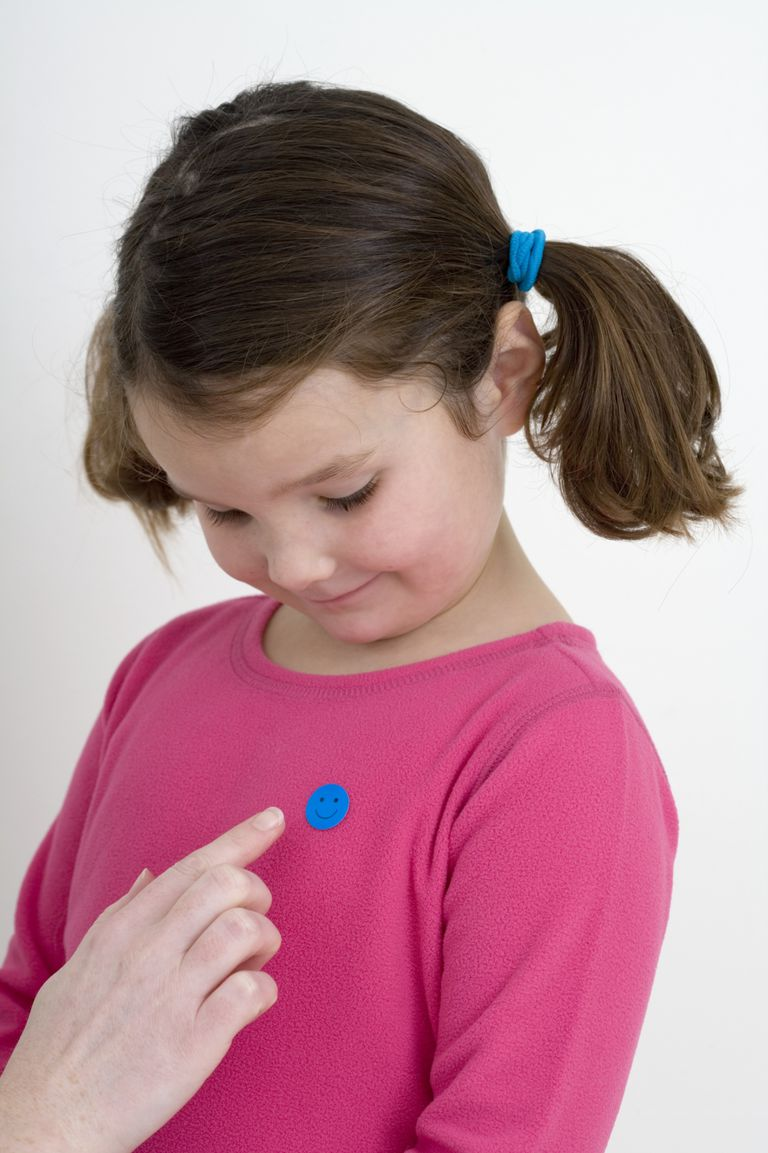 little girl getting reward sticker on shirt