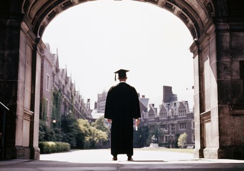 Graduate standing under an arch