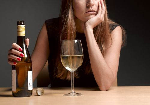 Woman resting her hand on her face, holding a bottle of wine