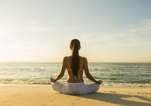 Woman meditating on a beach