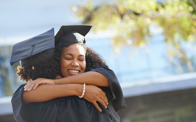 woman in graduation gown hugging someone