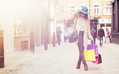 woman walking on street with shopping bags