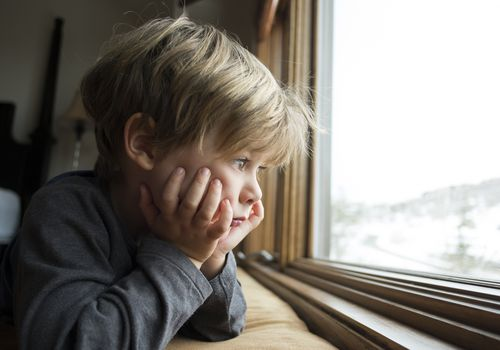 Sad looking boy looking out a window