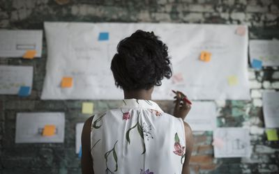 Woman brainstorming while looking at notes on office wall