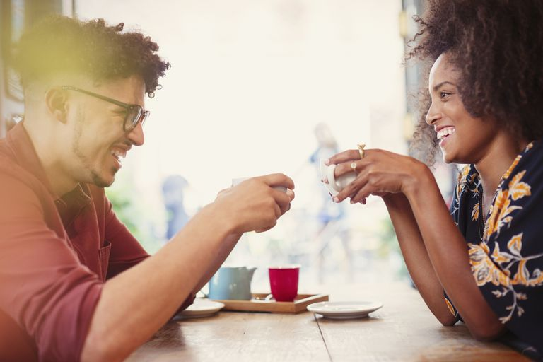 Couple drinking coffee face to face in cafe