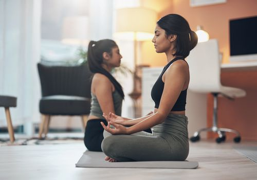 Shot of two young women meditating at home