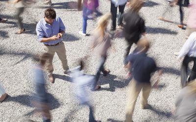 Man checking his cell phone among rushing crowd