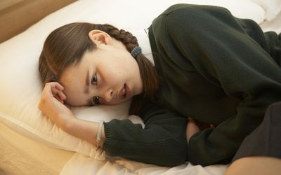 A young girl curled up on her bed