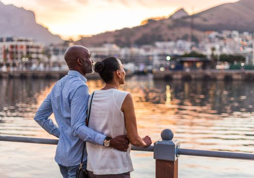Black man and woman looking out onto a pier