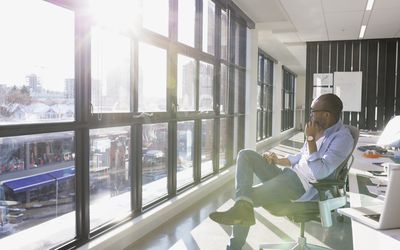 Pensive businessman looking out sunny office window